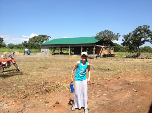 Avery in front of her families new home being built.